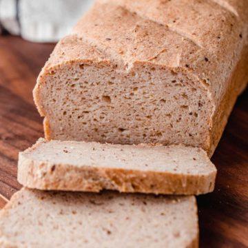 Una hogaza de pan de masa madre sin gluten sobre una tabla para cortar.