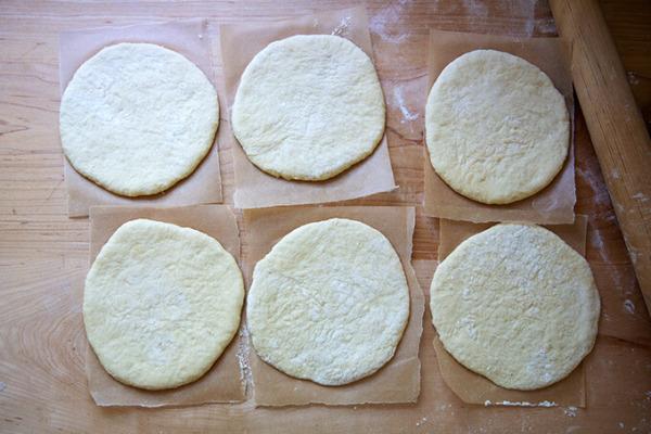 Seis rondas de pita sin hornear, cada una en una hoja de papel pergamino.