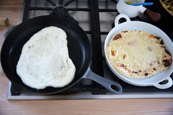 Una sartén de naan aparte de naan recién cocido.