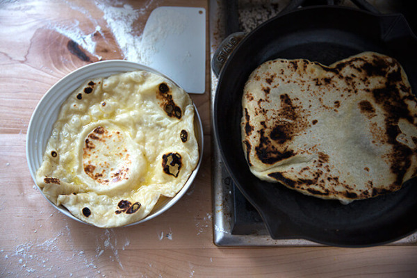 Una sartén de naan se cocina a un lado de un naan recién cocido en un tazón.
