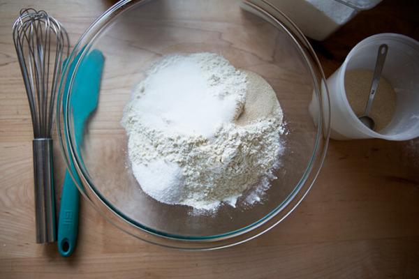 Una fotografía cenital de un recipiente de vidrio con los ingredientes secos para los panecillos de suero de leche.