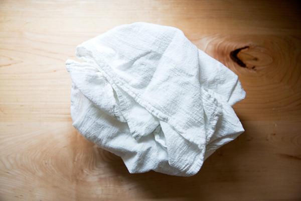 Un cuenco, forrado con un paño de cocina, relleno con una ronda de masa madre.
