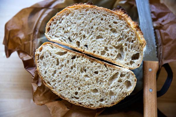 Una barra de pan de masa madre de alta hidratación a la mitad.
