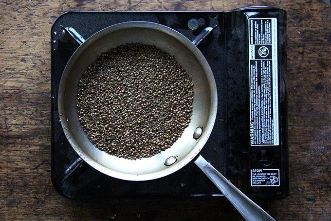 Una sartén con comino y semillas de cilantro en un quemador portátil.