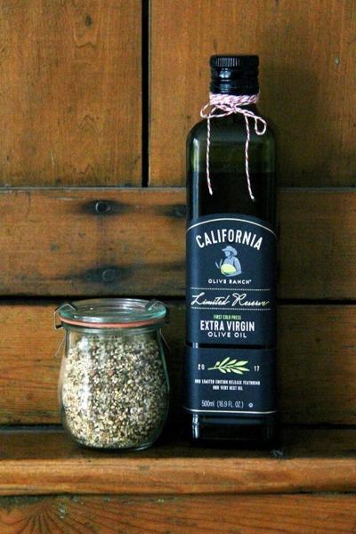 Una botella de aceite de oliva California Olive Ranch a un lado de un frasco de dukkah casero.