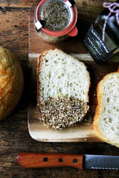 Una tabla con rebanadas de pan bañadas en aceite de oliva y dukkah.