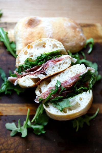 Un sándwich de prosciutto y rúcula a la mitad.